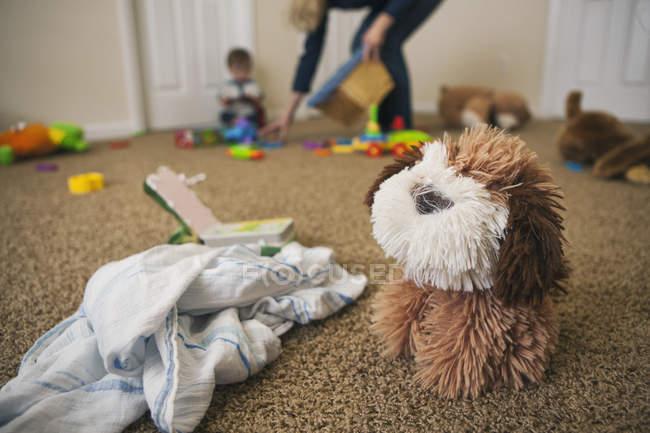 Cane giocattolo e stoffa su pavimento di camera dei bambini con madre che si schiarisce con figlio in disparte — Foto stock