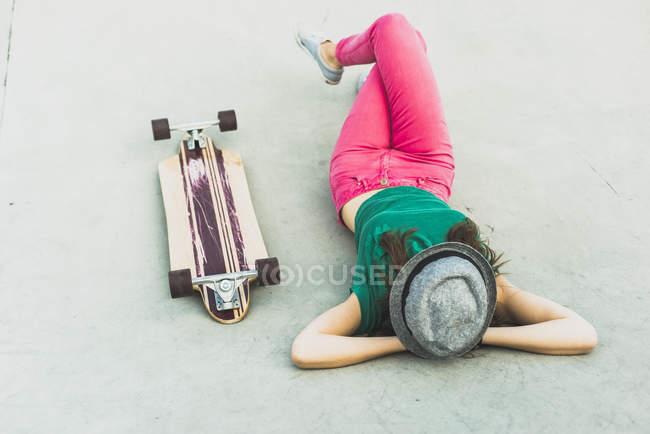 Молодая женщина, лежа помимо ее скейтборд отдыхающих — стоковое фото