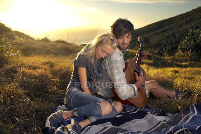 Pareja joven con guitarra en manta en prado - foto de stock