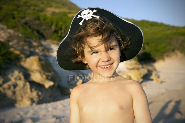 Портрет улыбающегося мальчика в пиратской шляпе на пляже — стоковое фото