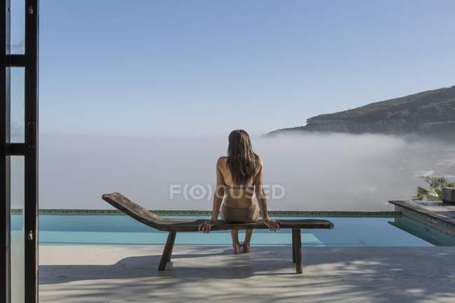 Женщина сидит в гостиной рядом с бассейном — стоковое фото