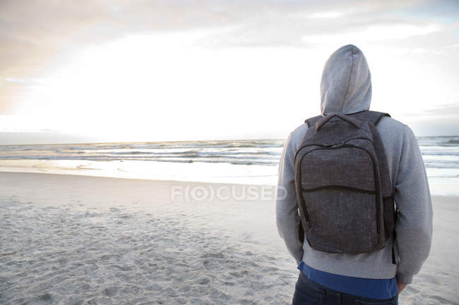 Young Man With Backpack On Beach At Sunrise One Person Rear View