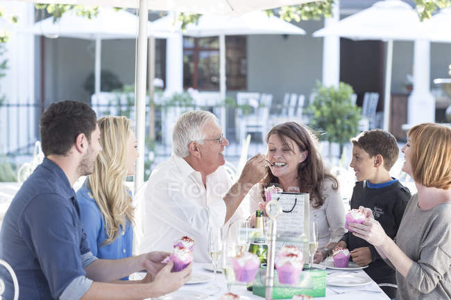 Three generations family celebrating grandfathers birthday at restaurant — Stock Photo