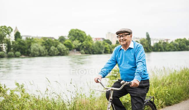 Smiling senior man riding bicycle — Stock Photo