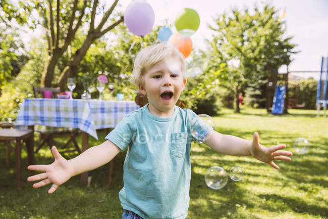 Boy trying to catch soap bubbles in garden — Stock Photo