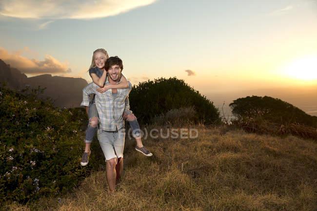 Young man carrying girlfriend piggyback at the coast — Stock Photo