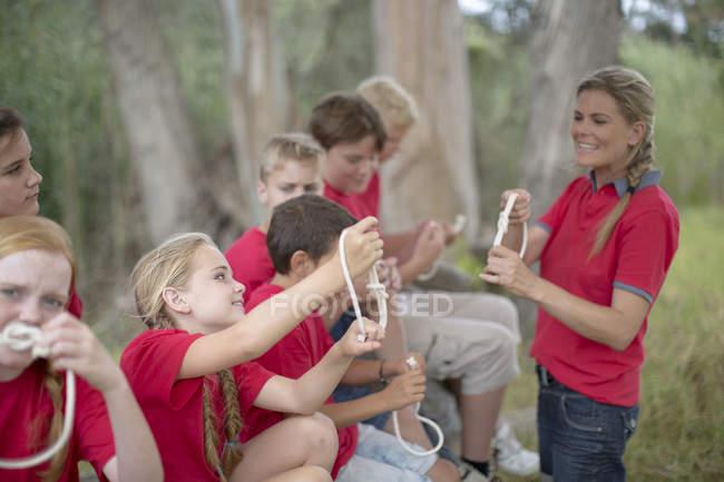 Женщина учит детей завязывать узлы — стоковое фото
