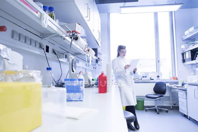 Jeune femme scientifique travaillant dans un laboratoire biologique protocole de lecture — Photo de stock
