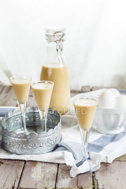 Close-up of three glasses and bottle of homemade egg liqueur placed on wooden table with bowl of eggs — Stock Photo