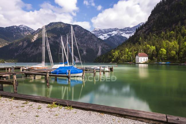 Austria, Tyrol, Ammergau Alps, Lake Plansee, harbor and mountains — Stock Photo
