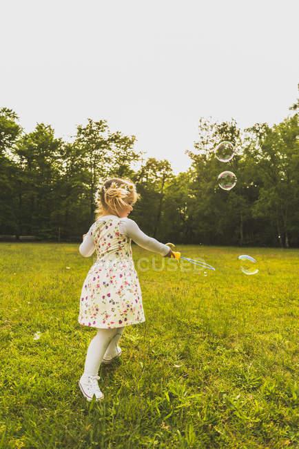 Девушка на лугу, окруженная мыльными пузырями — стоковое фото