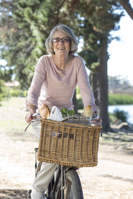 Portrait of senior woman on bicycle — Stock Photo