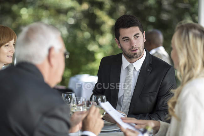 Елегантний людей у ресторані зовнішнім маючи в розмові — стокове фото