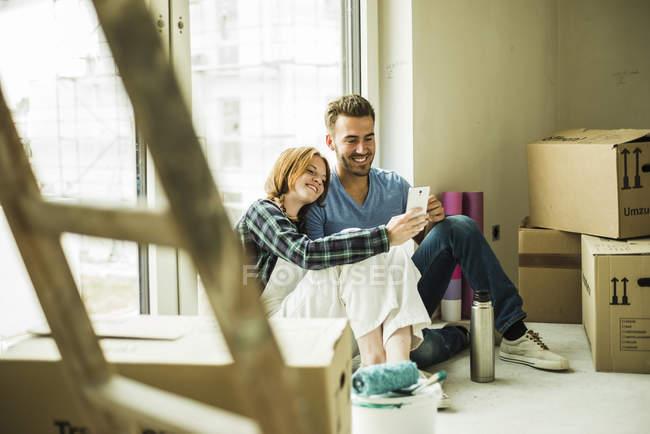 Улыбающаяся пара отдыхает от ремонта — стоковое фото