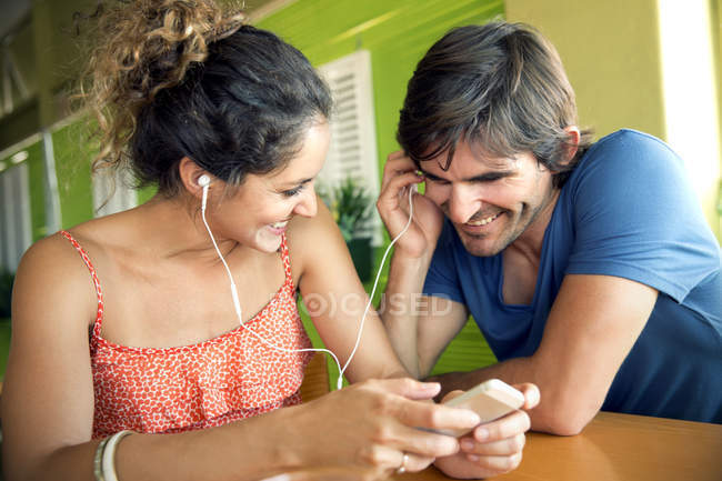 Happy couple in a cafe listening to music — Stock Photo