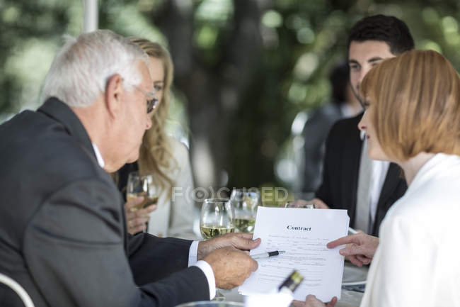 Elegant people at outside restaurant discussing a contract — Stock Photo