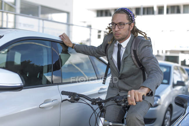 Businessman on bicycle in traffic jam — Stock Photo