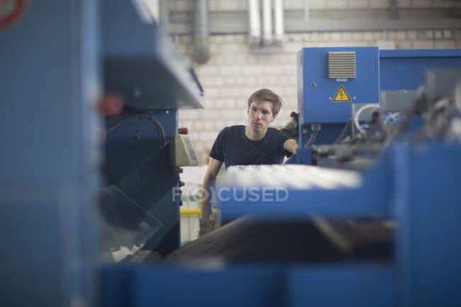 Technician in factory controlling machine — Stock Photo