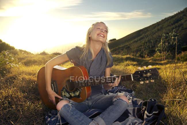 Счастливая девушка играет на гитаре на одеяле на лугу — стоковое фото