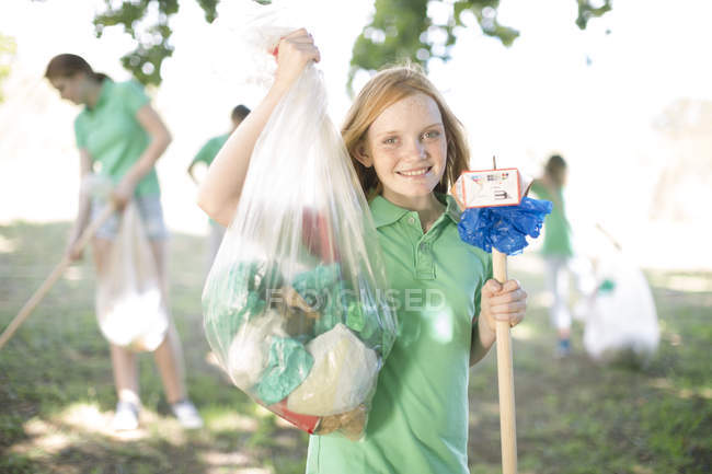 Portrait of smiling girl showing picked up garbage — Stock Photo