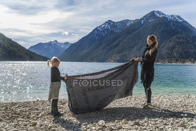 Austria, Tyrol, Lake Plansee, mother and daughter at lakeshore folding bath towel — Stock Photo