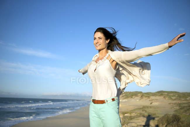 Lächelnde Frau mit ausgestreckten Armen stehen am Strand — Stockfoto