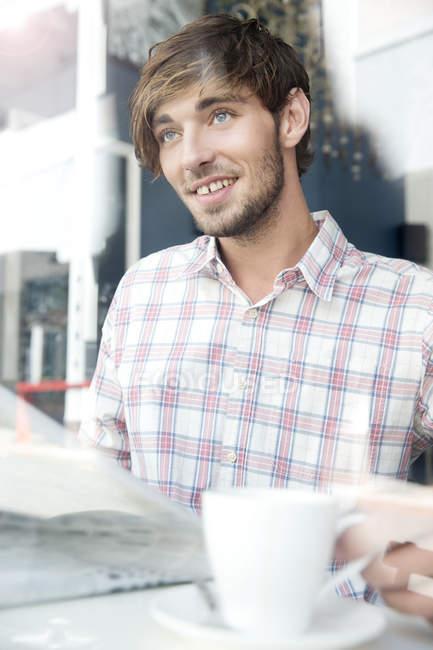 Lächelnder junger Mann in einem Café, der nach oben schaut — Stockfoto