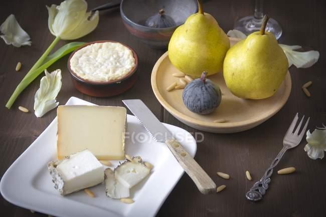 Різні сир, груші, інжир та кедровими горішками на коричневий дерев'яні поверхні — стокове фото