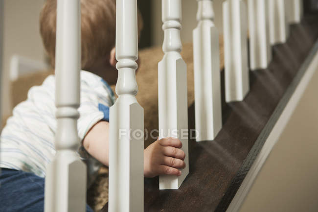 Hand of little boy climbing up staircase — Stock Photo