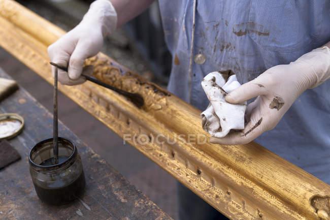 Изготовитель рамок в мастерской лакирует деревянную раму в стиле барокко — стоковое фото