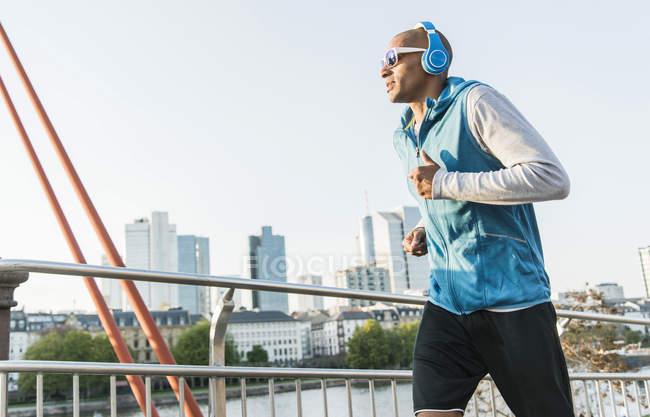 Germania, Francoforte, uomo con le cuffie che fa jogging sul ponte — Foto stock