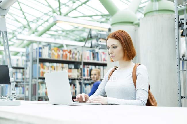 Студент в университетской библиотеке с ноутбуком — стоковое фото