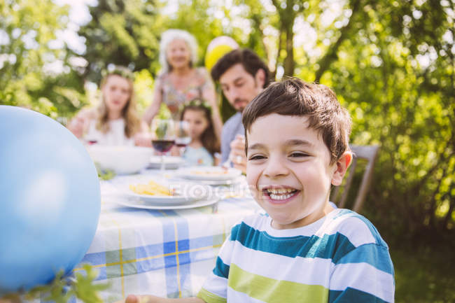 Happy boy on a garden party with family in bakground — Stock Photo