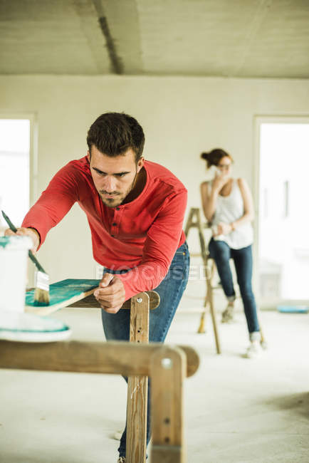 Young man painting wooden board with woman in background on the phone — Stock Photo