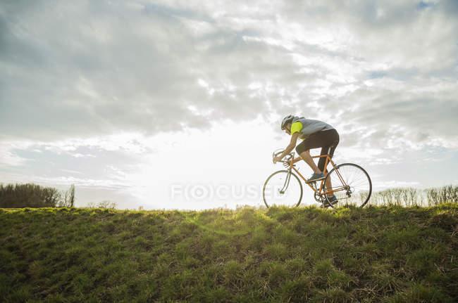 Giovane uomo in bicicletta nel prato — Foto stock