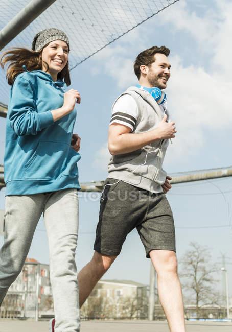 Sonriente pareja correr juntos al aire libre - foto de stock