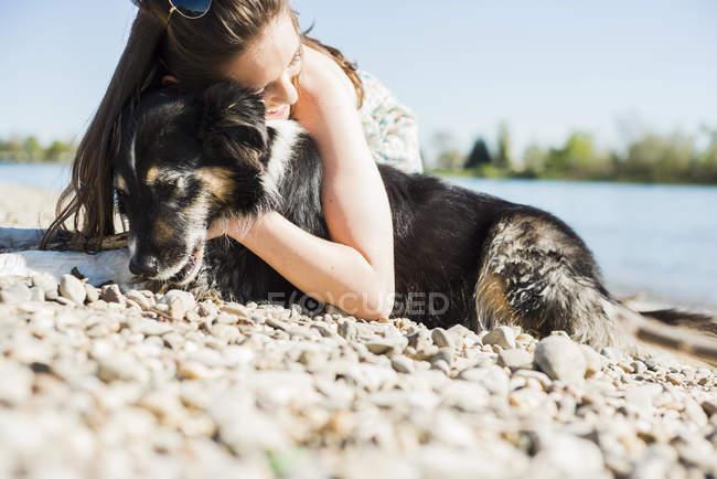 Jovem mulher abraçando com o cão em River Rhine, Alemanha, Mannheim — Fotografia de Stock