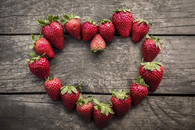 Erdbeeren in Herzform auf Holz — Stockfoto