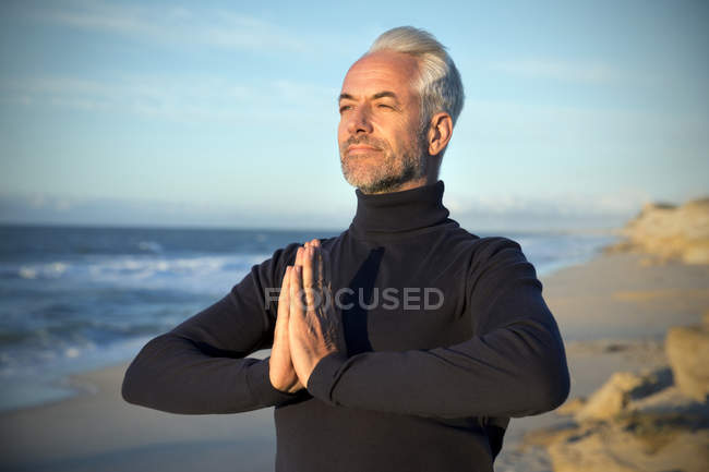 South Africa, portrait of man wearing turtleneck meditating on the beach before sunrise — Stock Photo