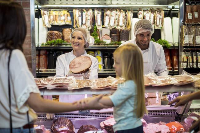 Client avec fille achetant du jambon à la boucherie — Photo de stock