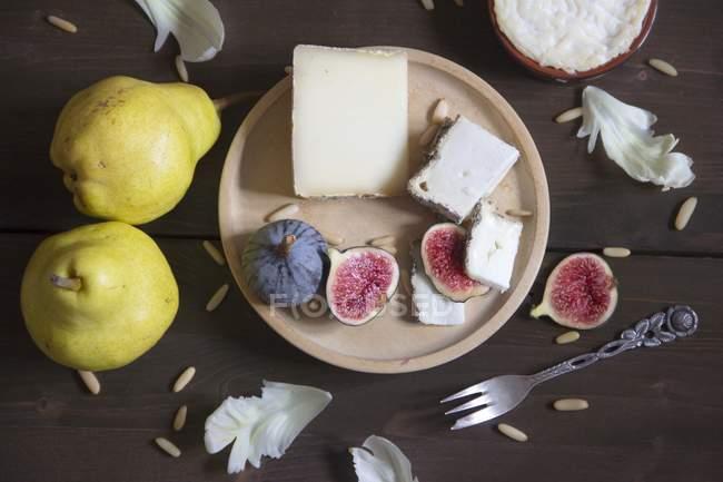 Різні сир, груші, інжир та кедровими горішками з плитою на коричневий дерев'яні поверхні — стокове фото