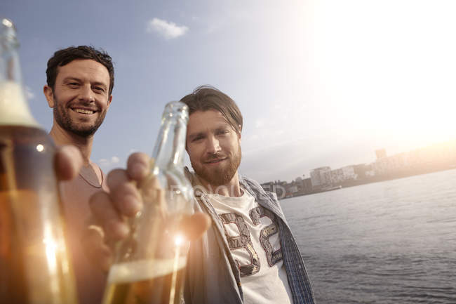 Portrait of two friends with beer bottles on riverbank — Stock Photo