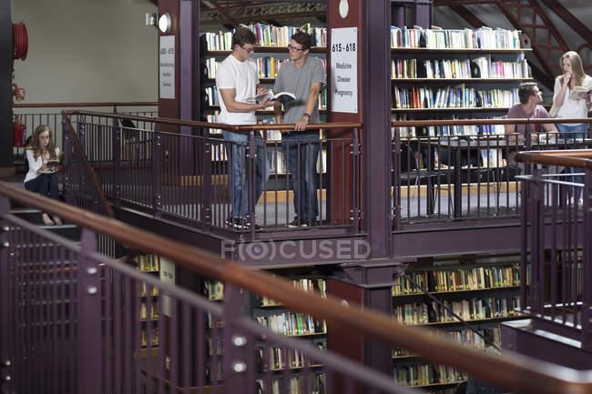 Jeunes étudiants caucasiens dans une bibliothèque regardant des livres — Photo de stock