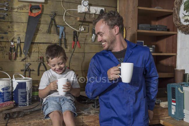 Батько і син, які працюють в будинку гараж, маючи перерва на каву — стокове фото