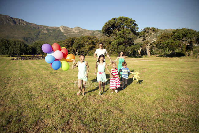 Happy family running with balloons on meadow — Stock Photo