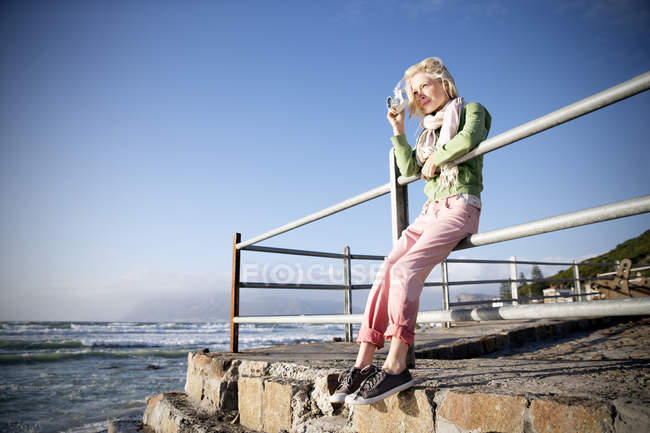 Young woman at the coast taking a picture — Stock Photo