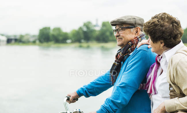 Senior couple with bicycle in front of water — Stock Photo
