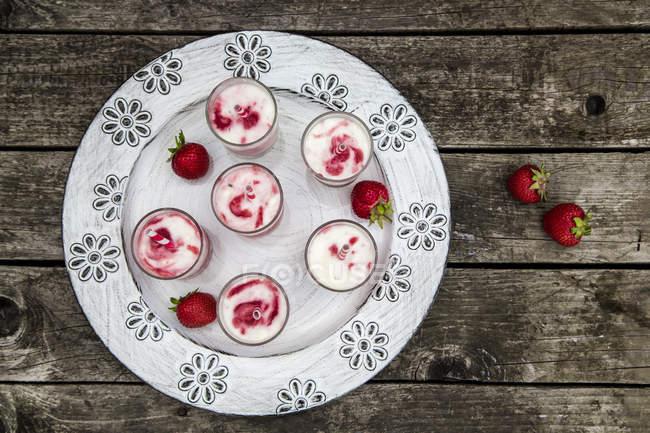 Vista superior de seis copos de sorvete de morango leitelho com bebendo palhas e morangos frescos no prato — Fotografia de Stock