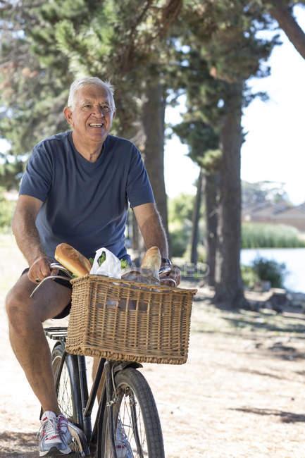 Smiling senior man on bicycle outdoors — Stock Photo