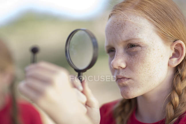 Girl on field trip looking through magnifying glass — Stock Photo